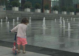 Regard d'un enfant avec trottinette en bordure de fontaine